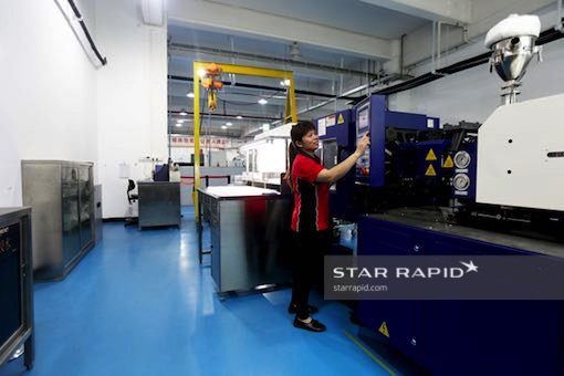 Worker operating plastic injection molding machine at Star Rapid